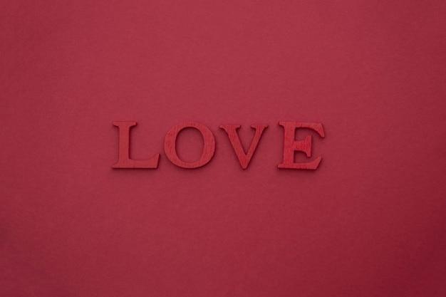 Love lettering, lettere rosse in legno 3d su rosso. san valentino creativo