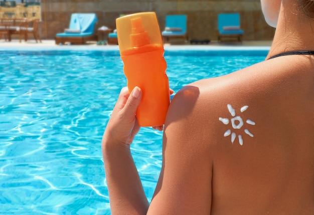 Lozione abbronzante. bella donna che applica la crema solare protezione solare a forma di sole. protezione solare. crema solare. crema solare idratante per la cura della pelle e del corpo.