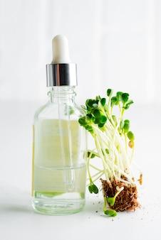 Lozione cosmetica fatta in casa o olio essenziale da microgreen naturale in bottiglia di vetro su sfondo grigio chiaro.