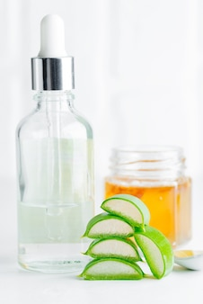 Lozione cosmetica fatta in casa o olio essenziale dalla pianta di aloe vera naturale affettata in bottiglie di vetro su sfondo grigio chiaro.