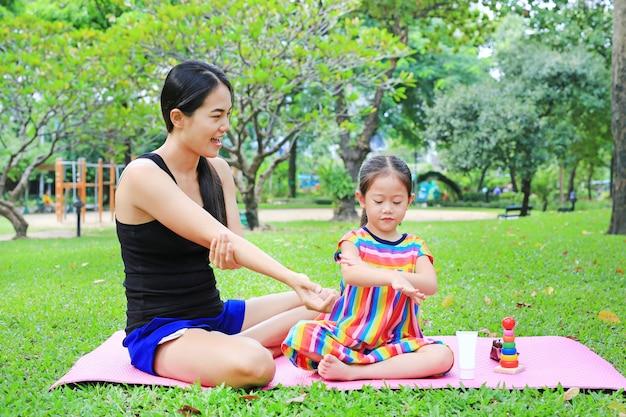 Lozione per il corpo appiccicosa della madre per la figlia nel parco estivo.