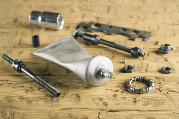 Lubrificante per bici con strumenti su un tavolo di legno.