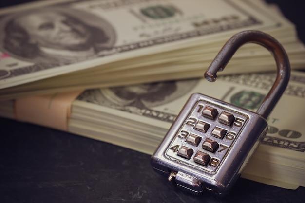 Lucchetto a combinazione e banconota da un dollaro nelle tenebre.