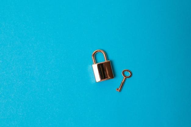 Lucchetto aperto e chiavi isolate su fondo blu