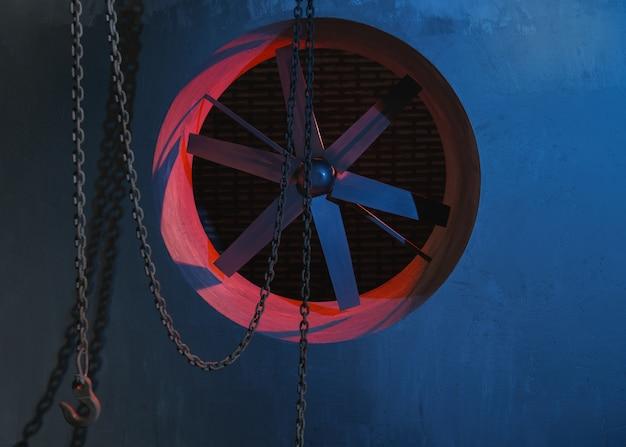 Luce al neon blu e rossa sulla ventola del sistema di ventilazione e catene con gancio di caricamento