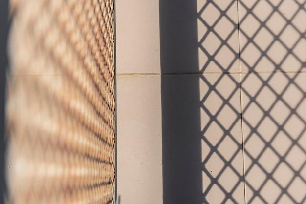 Luce del sole e ombra sfondo grigliato in acciaio