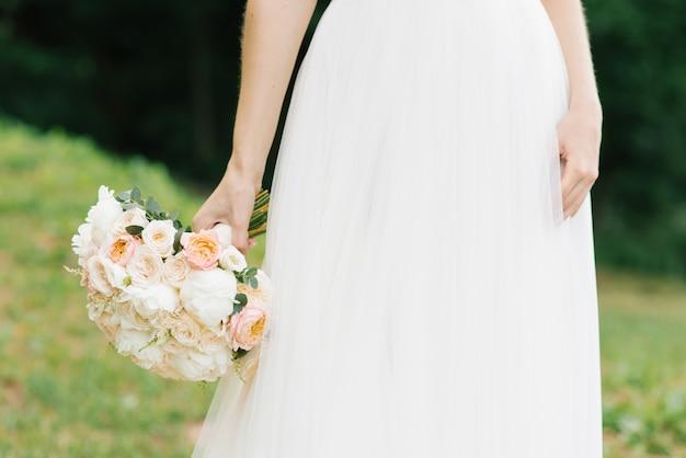 Luce delicata bouquet della sposa nelle mani della sposa