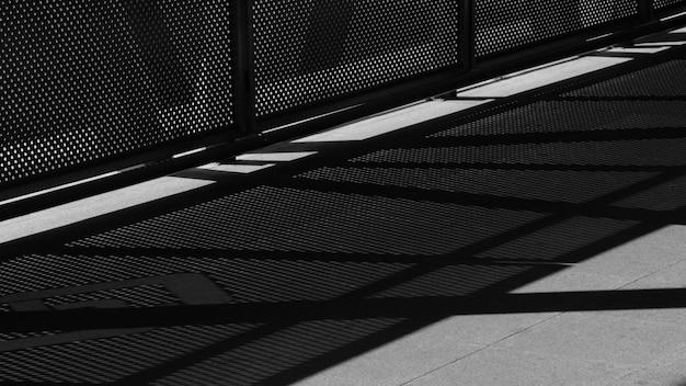 Luce e ombra della rete metallica sul marciapiede - monocromatico
