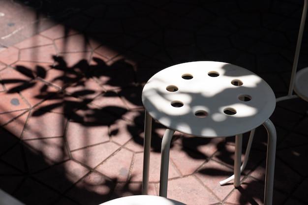 Luce e ombra su sgabello di plastica bianca all'esterno