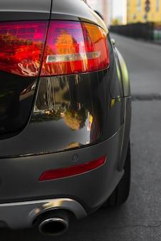 Luce posteriore elegante sulla nuova automobile nera sul percorso