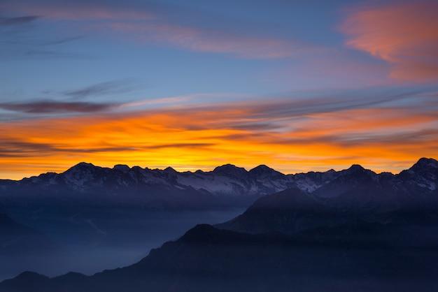 Luce solare colorata dietro le maestose cime delle alpi francesi italiane