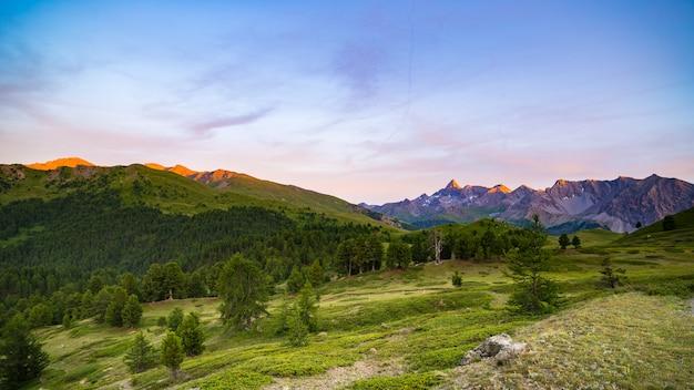 Luce solare colorata sulle maestose vette, boschi e valli delle alpi francesi italiane