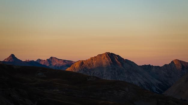 Luce solare colorata sulle maestose vette e creste delle alpi.