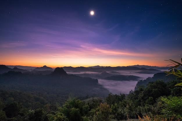 Luce solare del punto di vista sopra la montagna con la luna all'alba