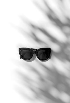 Luce solare estiva con ombra foglia di palma con occhiali da sole alla moda su sfondo bianco