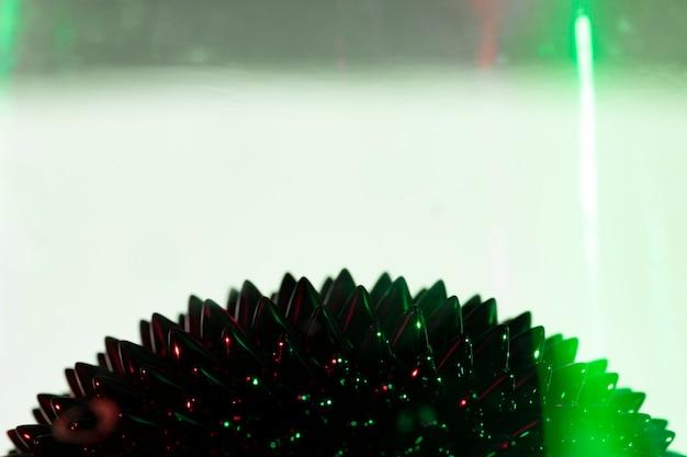 Luce verde e metallo liquido ferromagnetico con spazio di copia