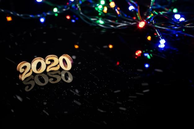 Luci brillanti del nuovo anno 2020 su sfondo scuro e spazio libero per il testo.