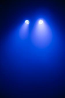 Luci da palcoscenico, riflettori puntati attraverso l'oscurità, effetti luminosi di scena spotlight, spettacolo di luci al concerto.