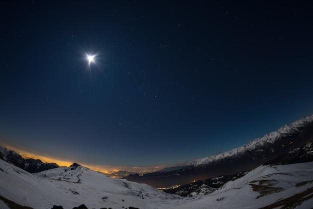 Luci della città di torino, vista notturna dalle alpi innevate al chiaro di luna. costellazione della luna e di orione, fisheye