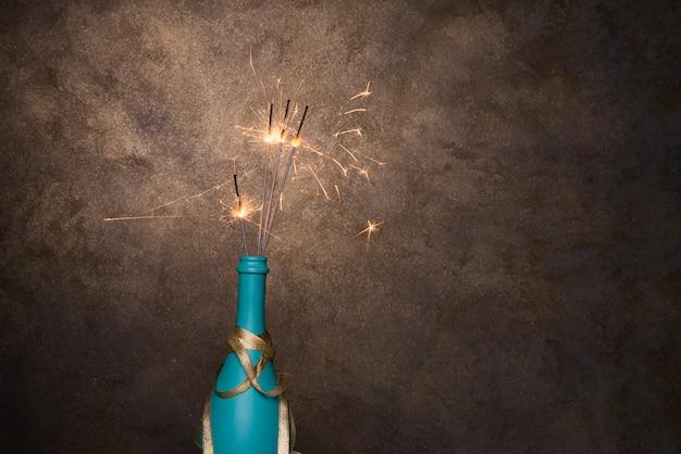 Luci di bengala fiammeggiante in bottiglia di bevanda