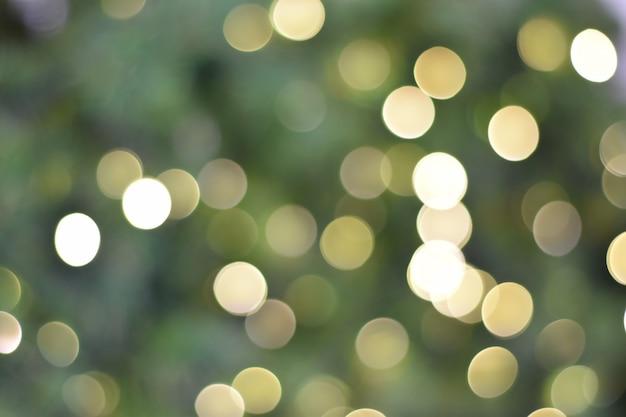 Luci dorate e verdi di natale. sfondo di bokeh brillante.
