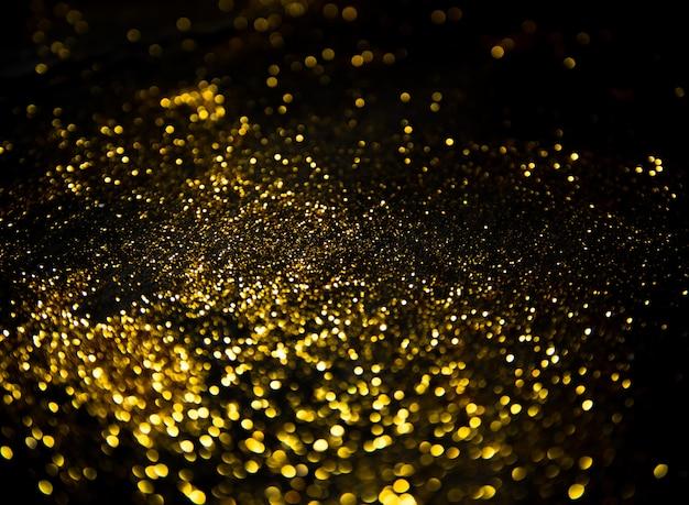 Luci glitter dorate su fondo nero