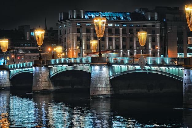 Luci notturne sul ponte per san pietroburgo. illuminazione serale della città.