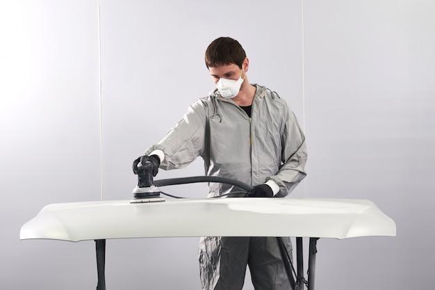 Lucidatura del cappuccio del meccanico automatico e cappuccio di lucidatura dell'automobile nell'officina riparazioni automatica
