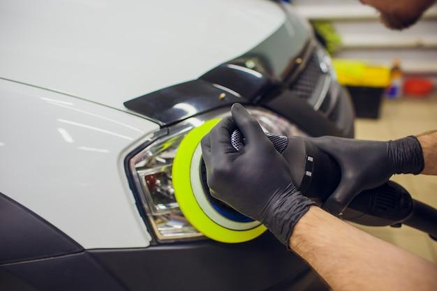 Lucidatura del meccanico auto e lucidatura del faro dell'auto