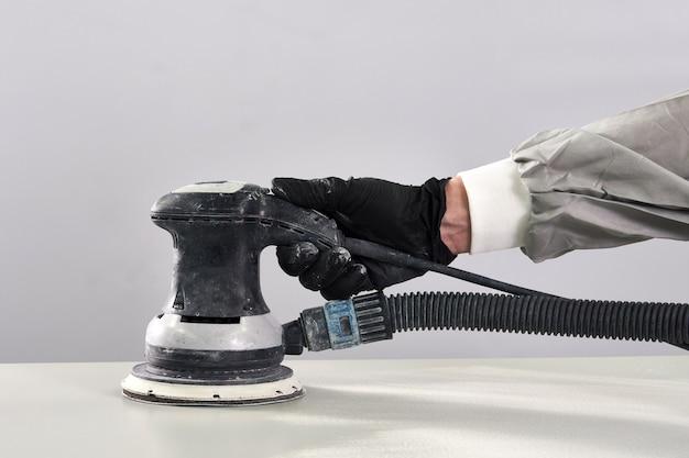 Lucidatura e lucidatura del meccanico auto in officina riparazioni auto con lucidatore orbitale, pulizia di base dello strato