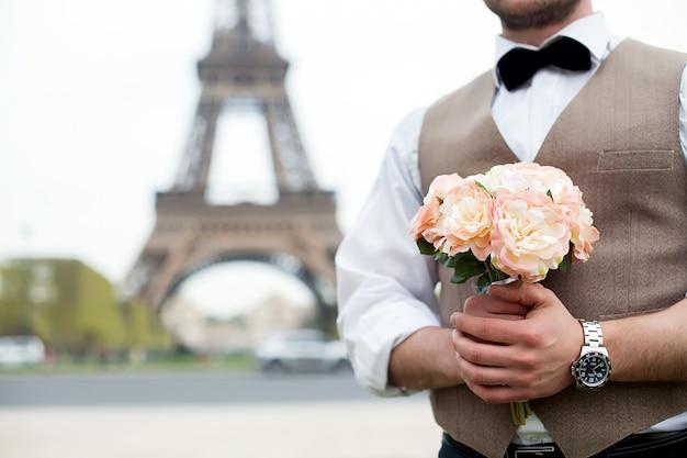 Lui sposa con in mano un mazzo di fiori