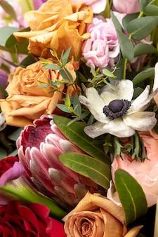 Luminoso bouquet combinato di protea, rose, anemone coronaria, eucalipto. avvicinamento.