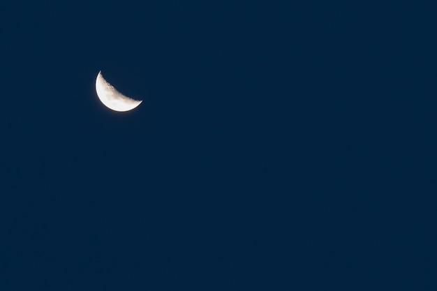 Luna crescente sopra il fondo del cielo blu di mezzanotte