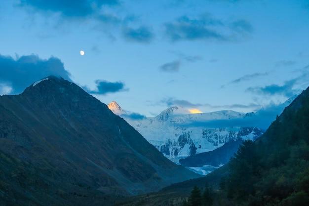 Luna sopra la dorsale montuosa di akkem. paesaggio notturno monti altai, russia
