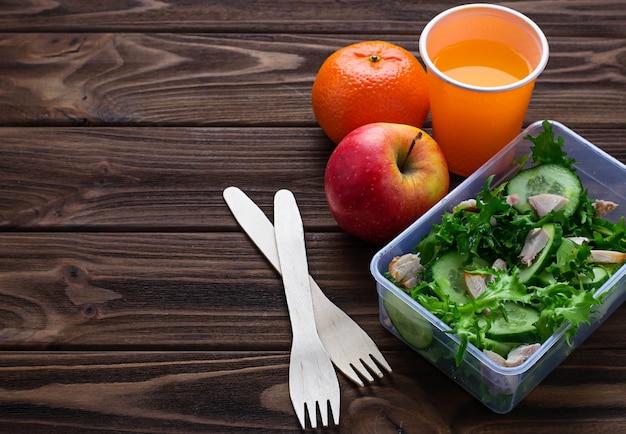 Lunch box con insalata, mela, mandarino e succo di frutta.