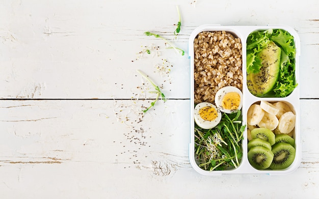 Lunch box con uova sode, farina d'avena, avocado, micro verdure e frutta.