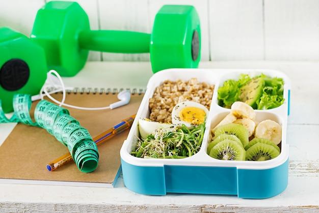 Lunch box con uova sode, fiocchi d'avena, avocado, micro verdi e frutta. cibo sano fitness porta via. sacco per il pranzo.