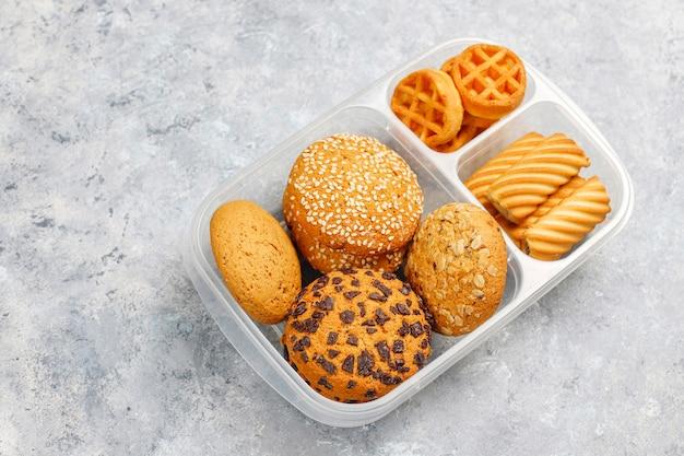 Lunch box malsano con biscotti, waffles.muffins sulla superficie del calcestruzzo