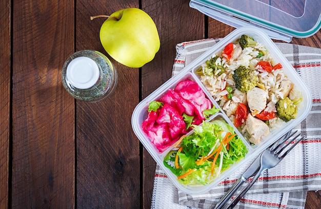 Lunch box pollo, broccoli, piselli, pomodoro con riso e cavolo rosso