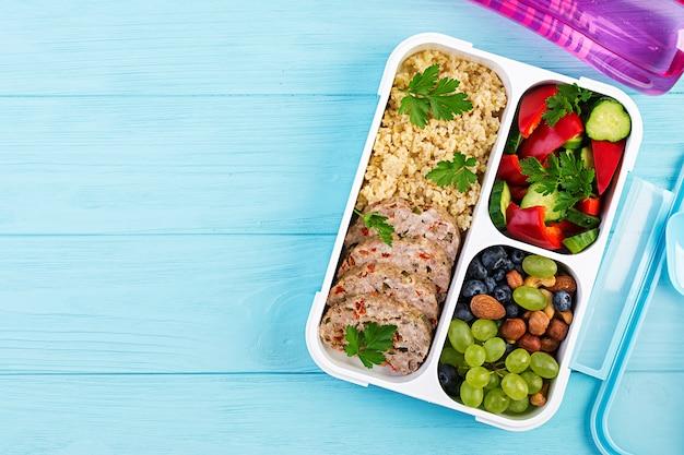 Lunch box polpettone, bulgur, noci, cetrioli e bacche. cibo fitness sano. porta via. sacco per il pranzo. vista dall'alto
