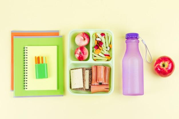 Lunchbox con cibo, bottiglia d'acqua, quaderni sul desktop in legno, vista dall'alto