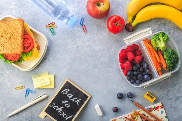 Lunchbox con la bottiglia dei broccoli delle carote delle bacche del panino della banana dell'acqua sulla vista superiore grigia