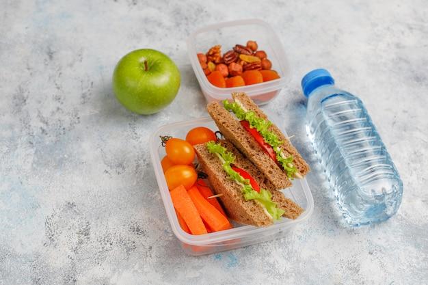 Lunchbox con sandwich, verdure, frutta su bianco.