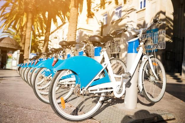 Lunga fila di biciclette a noleggio parcheggiate in una strada