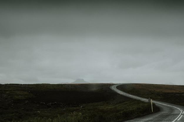 Lunga strada sinuosa nel mezzo di un campo verde in islanda
