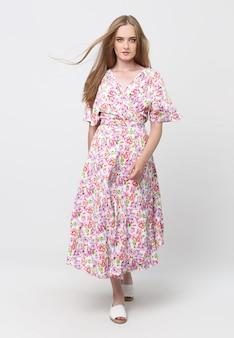 Lunghezza intera di una giovane ragazza elegante in un abito estivo leggero, in uno spazio luminoso. concetto pubblicitario per negozi di abbigliamento. contenuti per social network e banner.