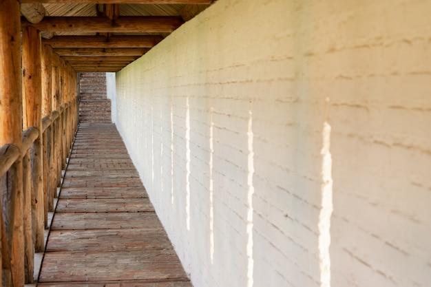 Lungo passaggio nel monastero sullo sfondo del muro di pietra bianca.