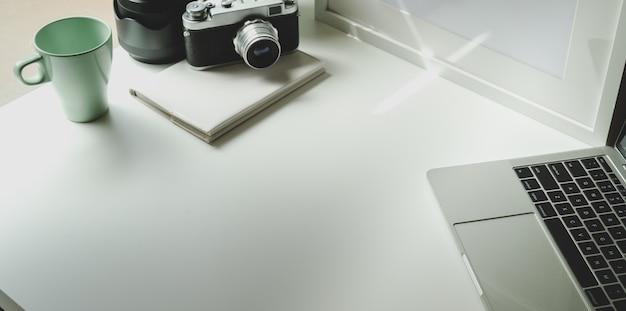 Luogo di lavoro alla moda fotografo con tablet e macchina fotografica d'epoca