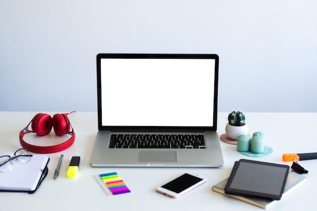 Luogo di lavoro con laptop vicino a smartphone, tablet, notebook e cuffie
