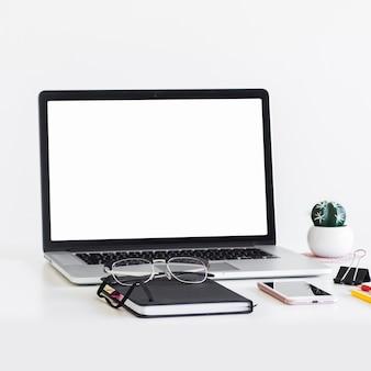 Luogo di lavoro con laptop vicino occhiali, blocco note e telefono cellulare